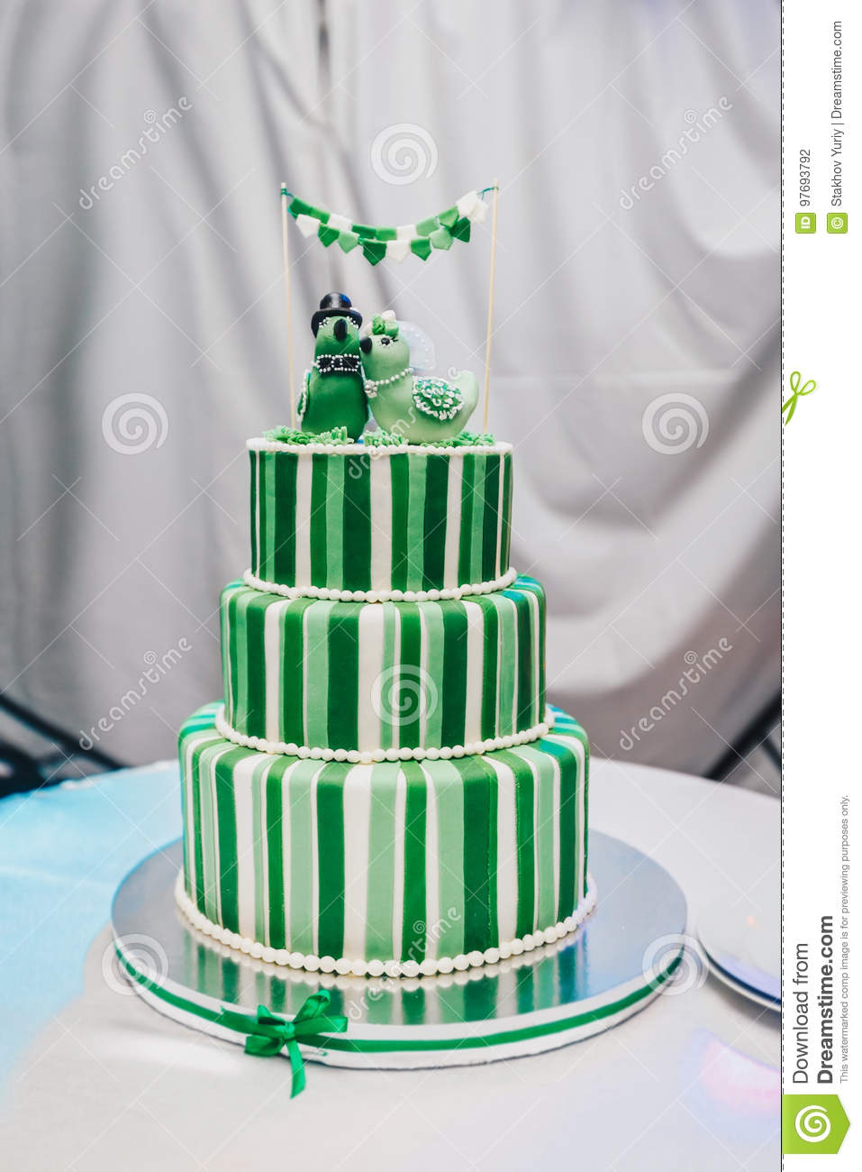 Beautiful big three leveled wedding cake decorated with two birds on the top. A green-white striped wedding cake with