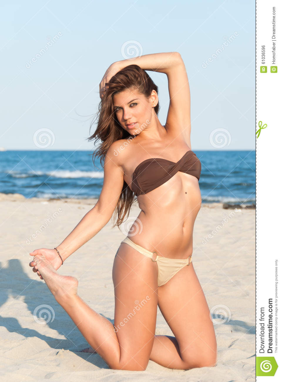 6c080ba5cfd Beautiful bikini model posing on the beach. Wear two pieces swimsuit,  attractive body with brunette long hair. Kneeling on sand, holding hair and  toes, ...