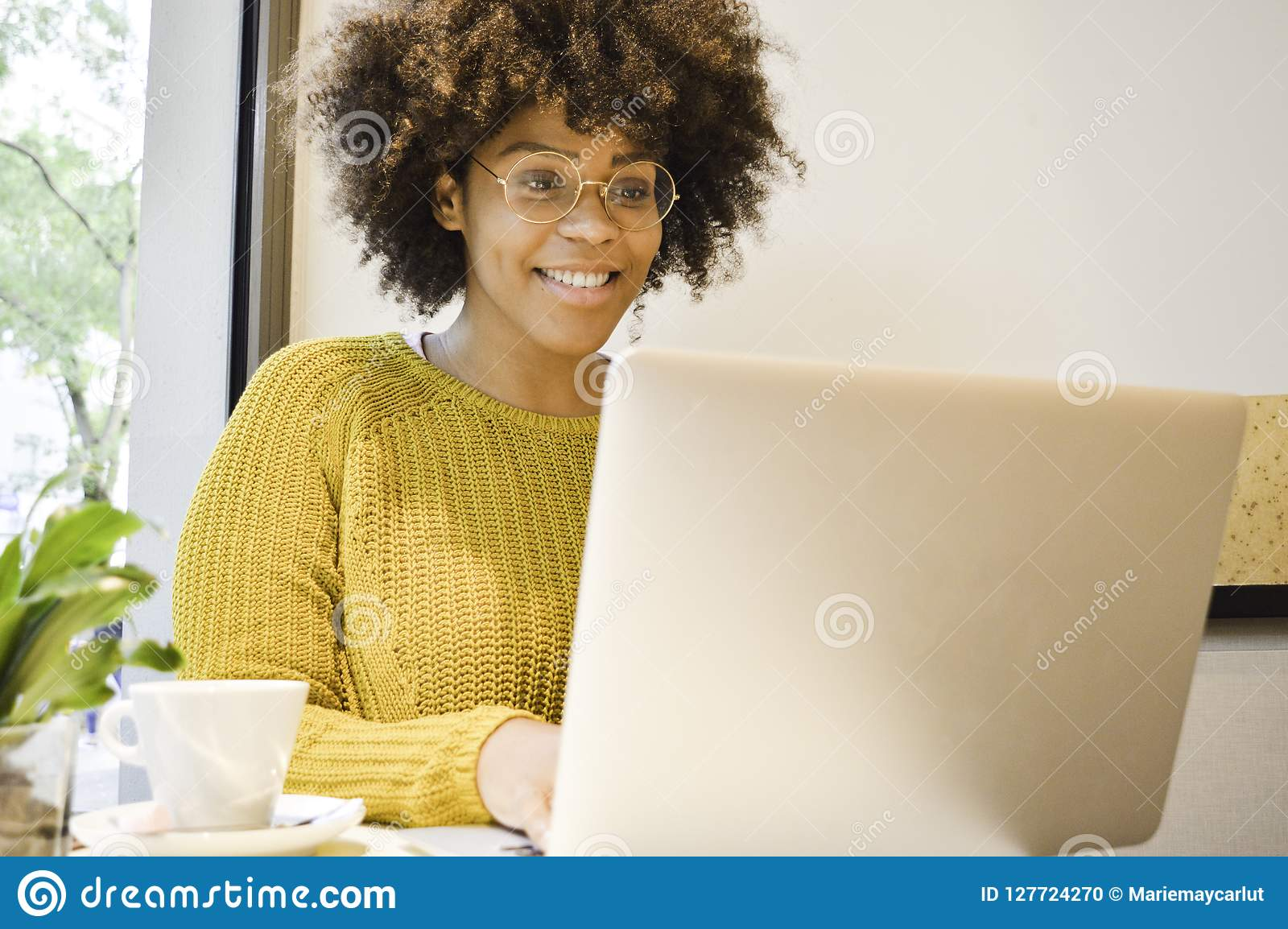 Beautiful black student woman smiling at the laptop drinking coffee