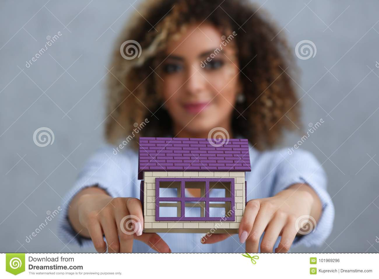 Beautiful Black Woman Portrait Holds A Miniature Toy Doll House