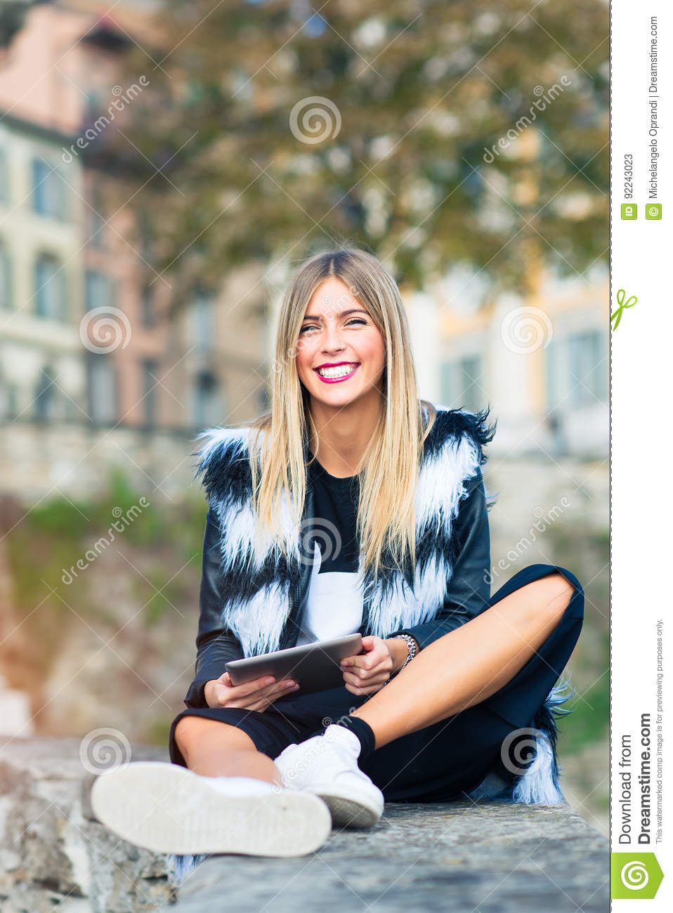 Beautiful blond girl with a big big smile and tablet in hand