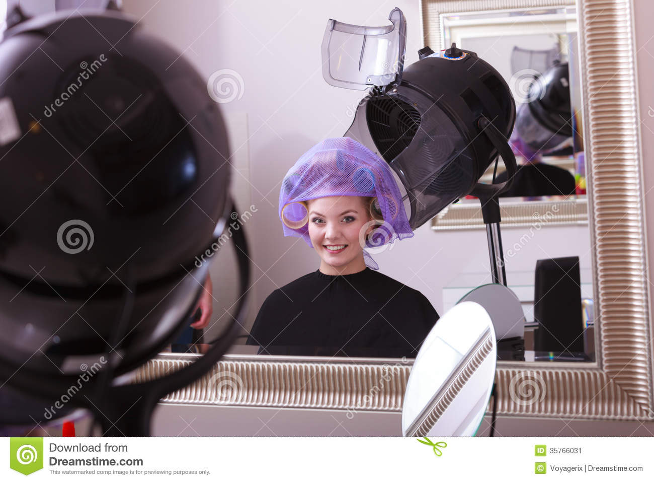 Beautiful young woman in beauty salon blond girl with hair curlers