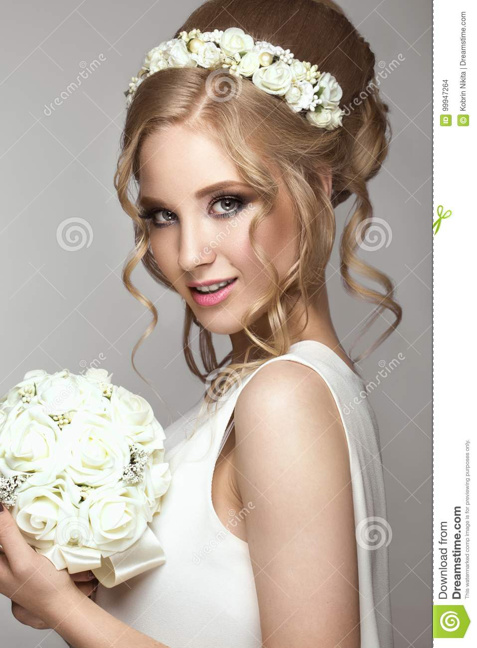 Beautiful blond girl in image of the bride with white flowers on her head. Beauty face.
