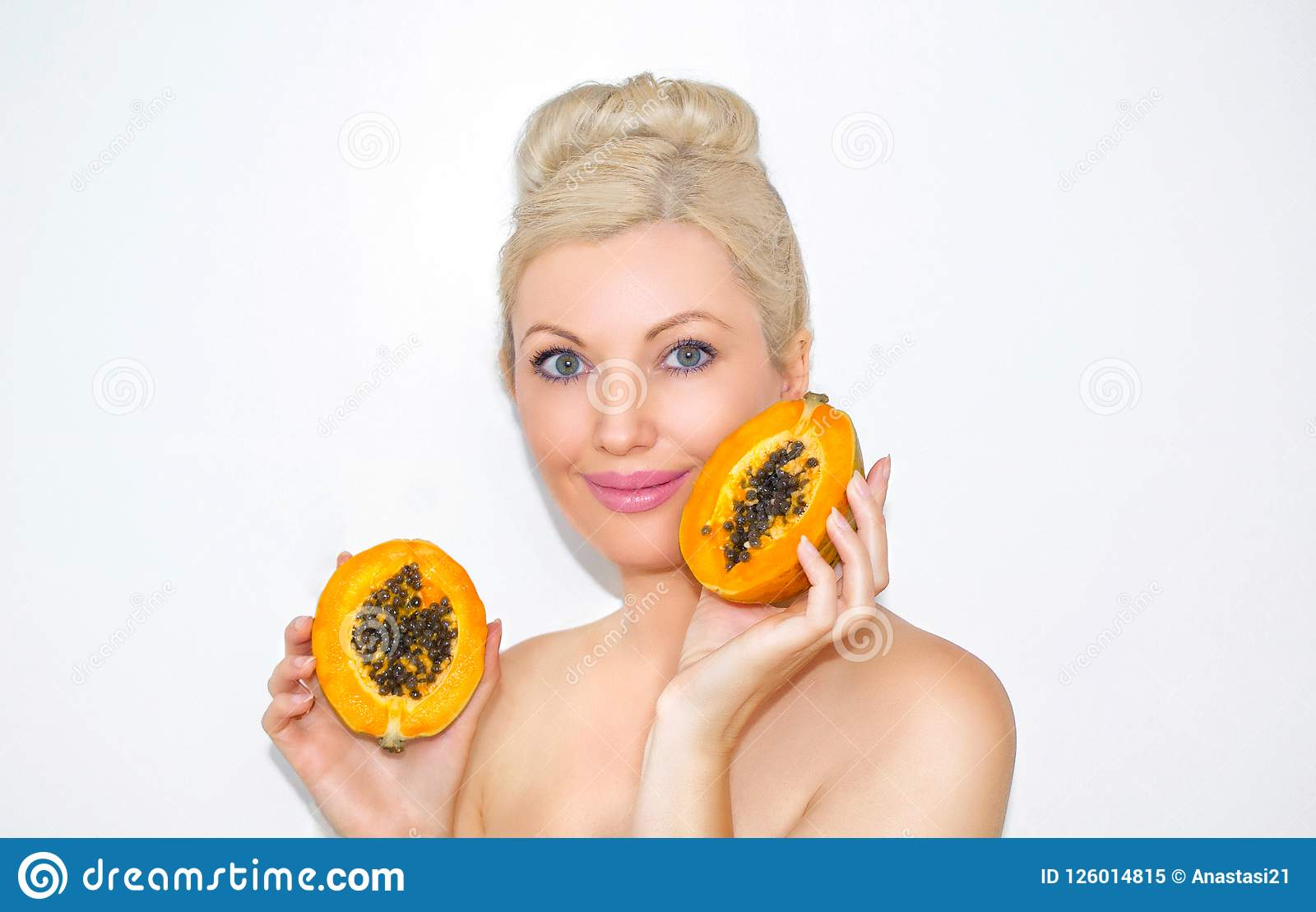Beautiful young blond woman with papaya in hands. The concept of healthy skin and moisturizing. Advantages of fruit.
