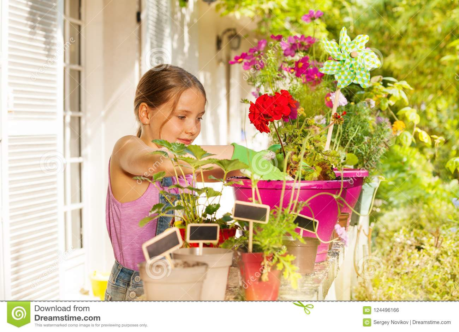 Beautiful blond girl potting geranium on terrace