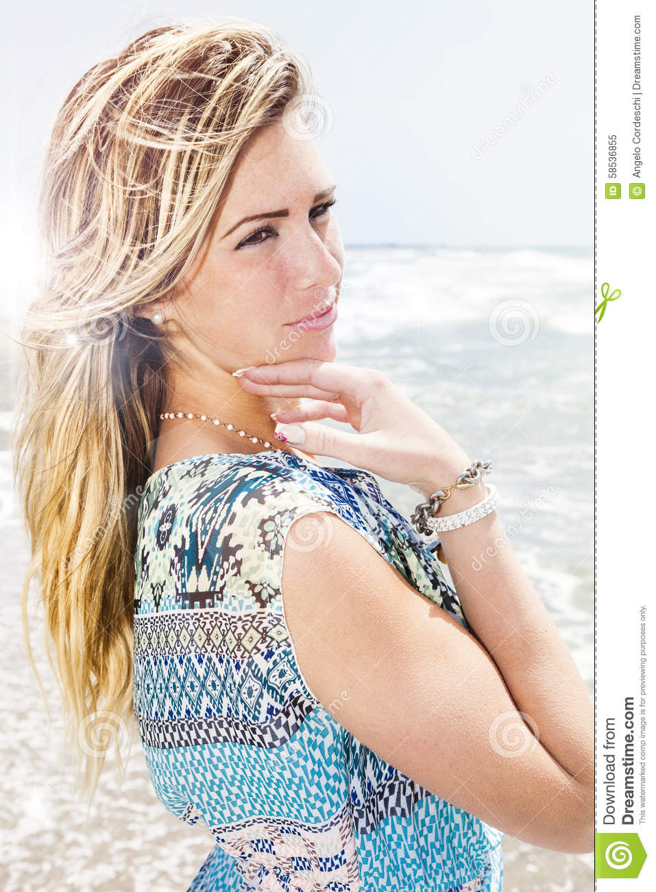 Beautiful blonde girl with sea background. Sweet attitude