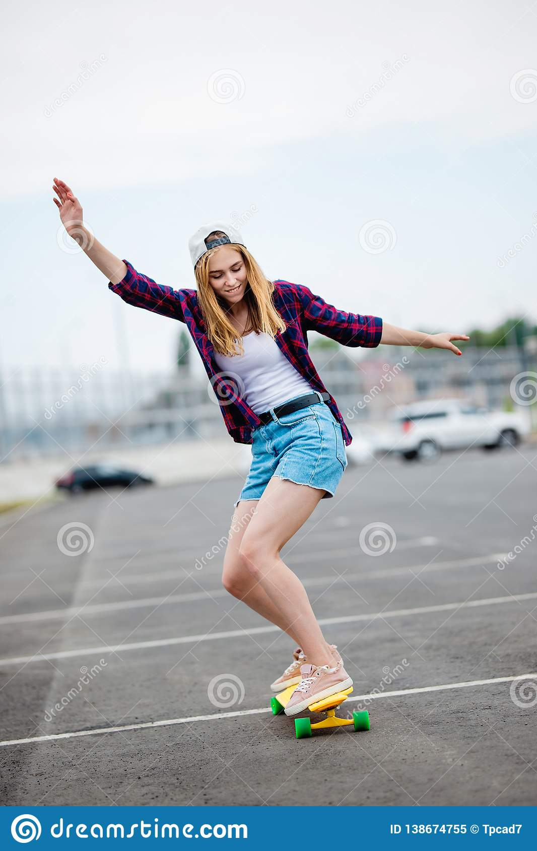 A beautiful blond girl wearing checkered shirt, cap and denim shorts is longboarding while stretching out her hands