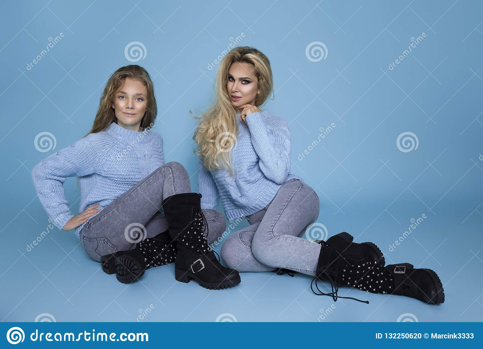 Beautiful blond girls, mother with daughter in autumn winter clothing on a blue background in the studio