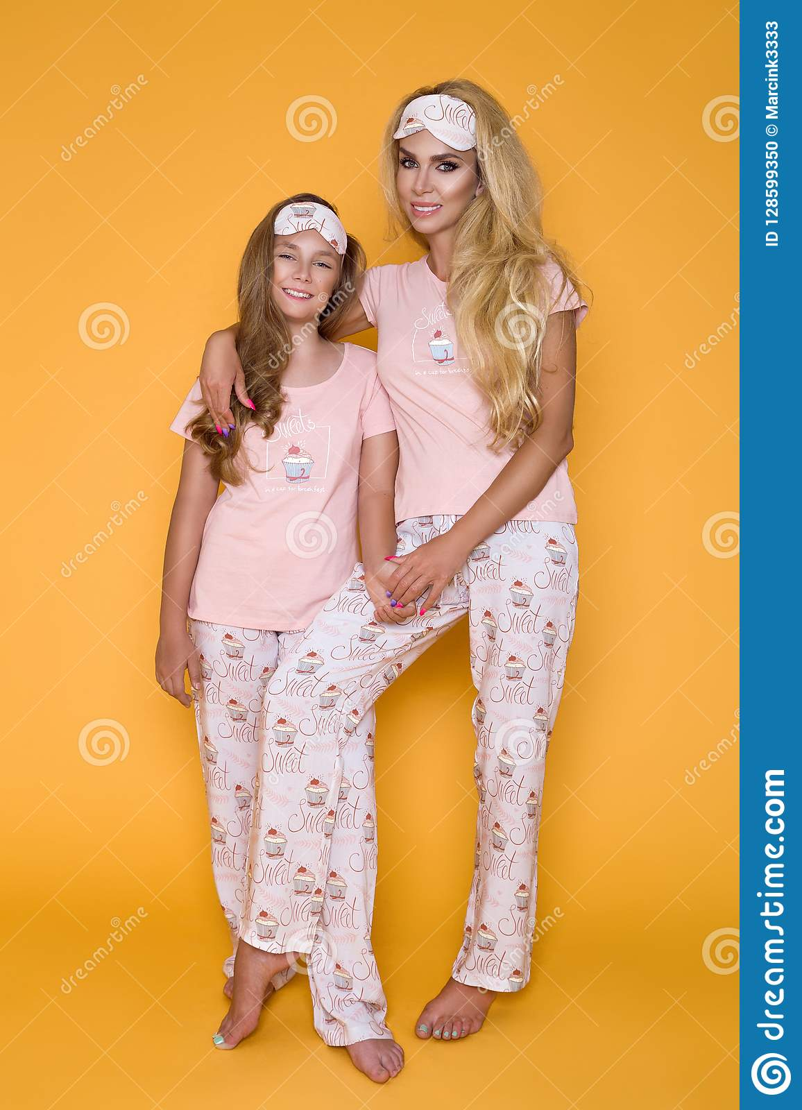 Beautiful blond girls, mother with daughter in pajamas on a yellow background in the studio.