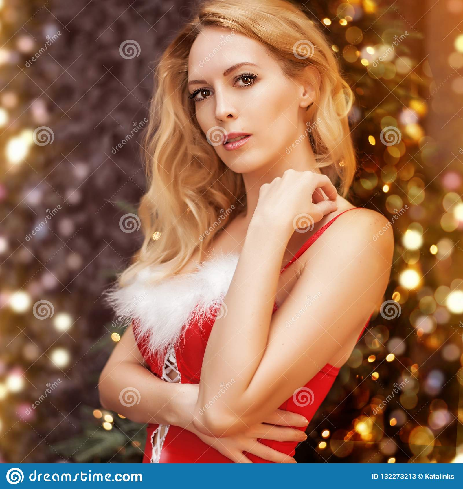 Beautiful blond woman in red christmas dress with white fur on breast stay  near christmas eve with lights and decorations. Portrait
