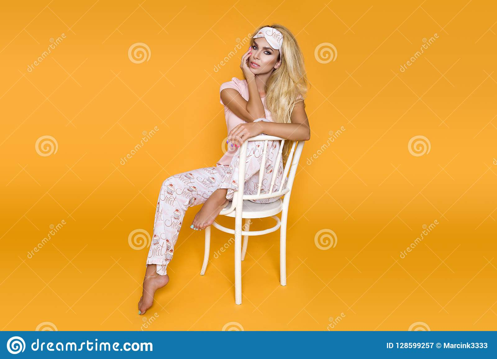 Beautiful blond woman in pajama on a yellow background in the studio.