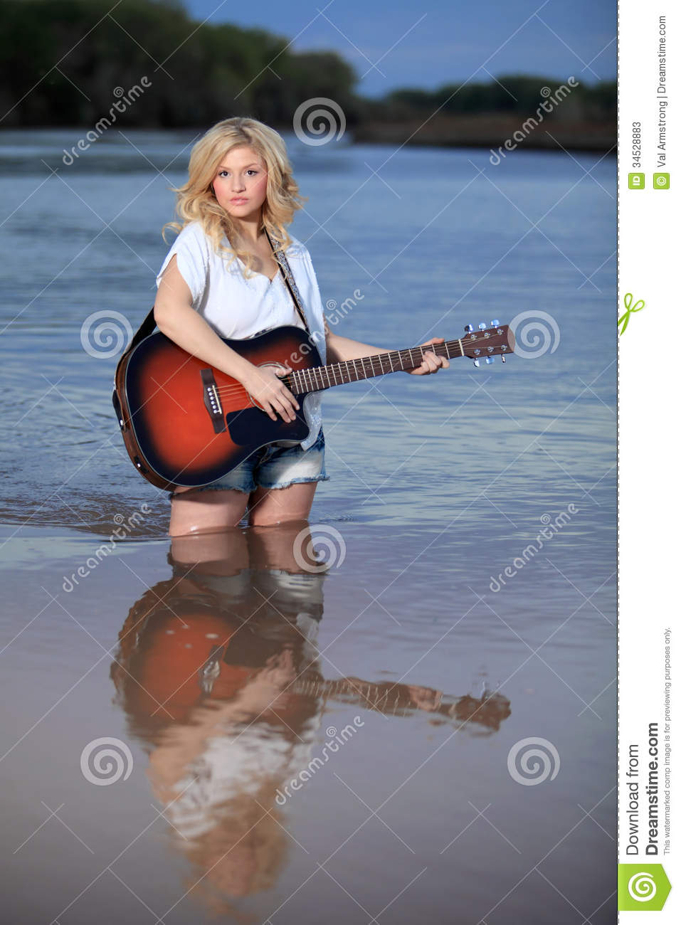 Beautiful Blond Woman Playing Acoustic Guitar In Water Stock Image