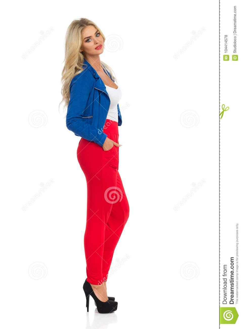 Beautiful Blond Woman Is Standing In Red Pants, Blue Jacket And High Heels. Side View.
