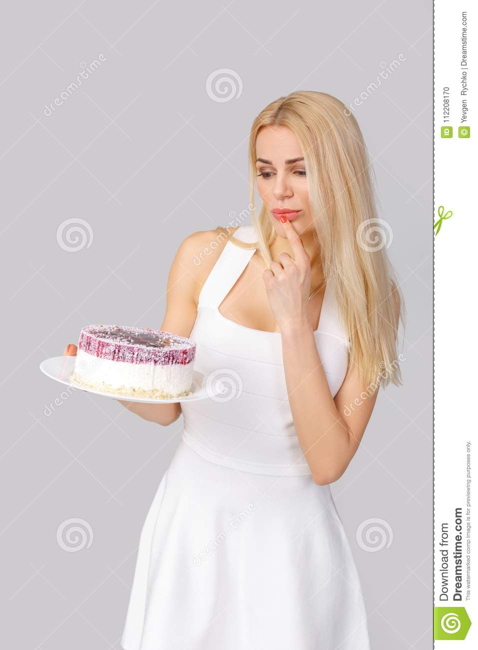 Woman in white dress holding cake