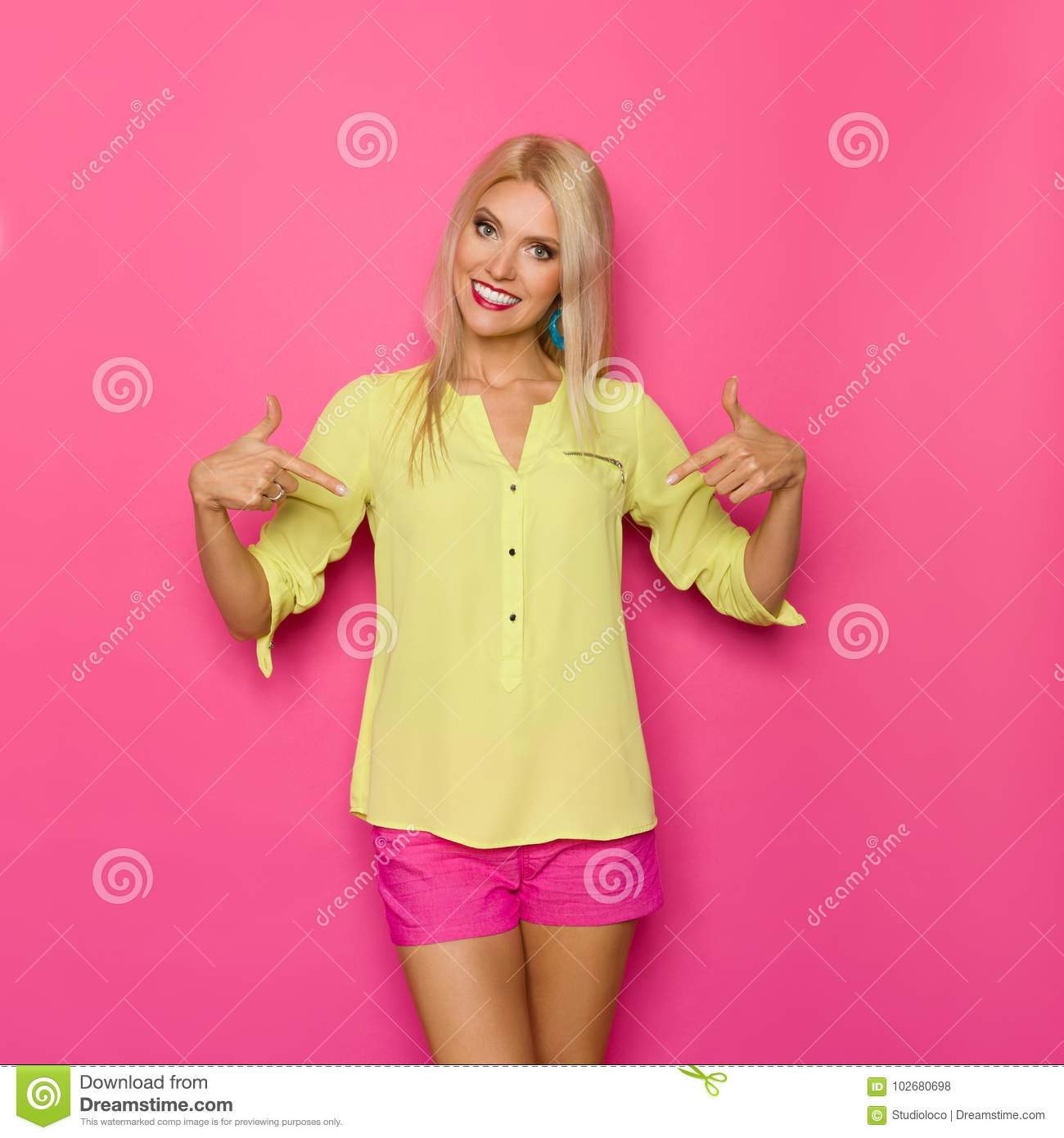 f3939d4687ac04 Beautiful blond young woman in yellow shirt and pink shorts is smiling and  pointing at her torso. Three quarter length studio shot on pink background.