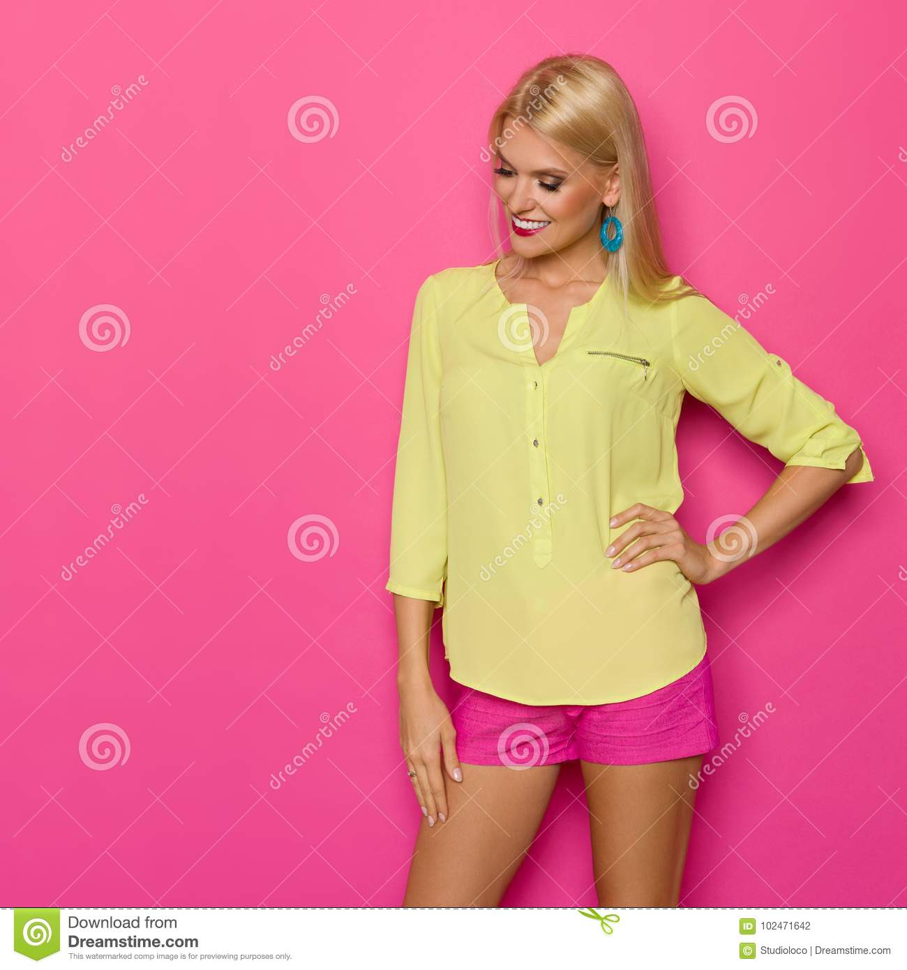 b7685bafa542f Beautiful blond young woman in yellow shirt and pink shorts is standing  with hand on hip