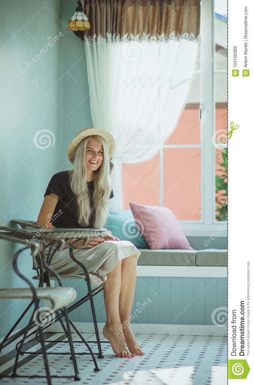 pretty young woman sitting on waiting room chair stock photo