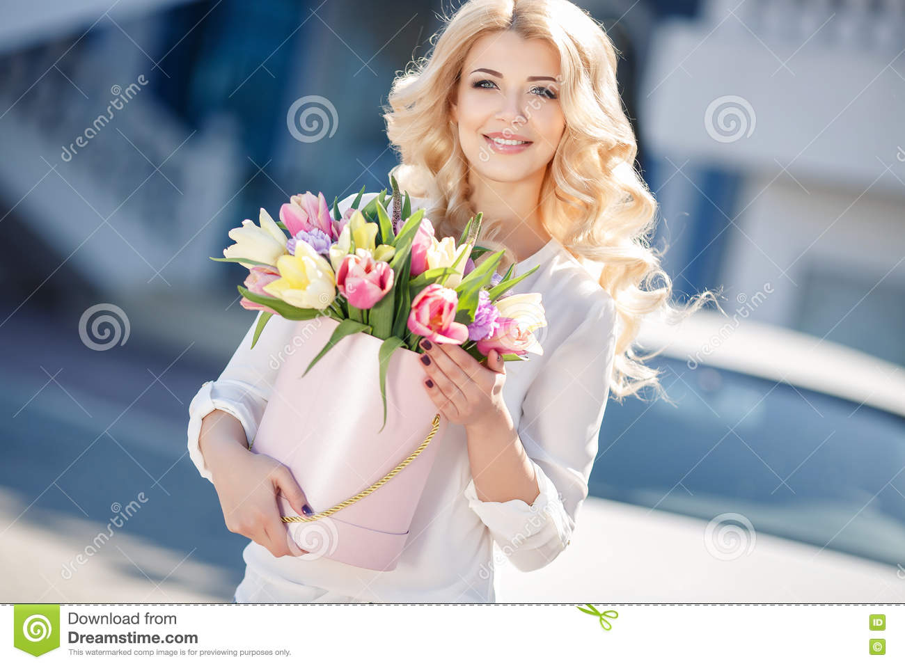 Beautiful blonde with flowers in gift box