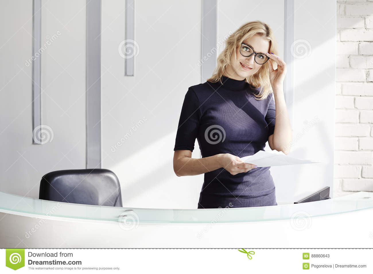 Beautiful blonde friendly woman behind the reception desk, administrator talking by phone. Sunshine in modern office.