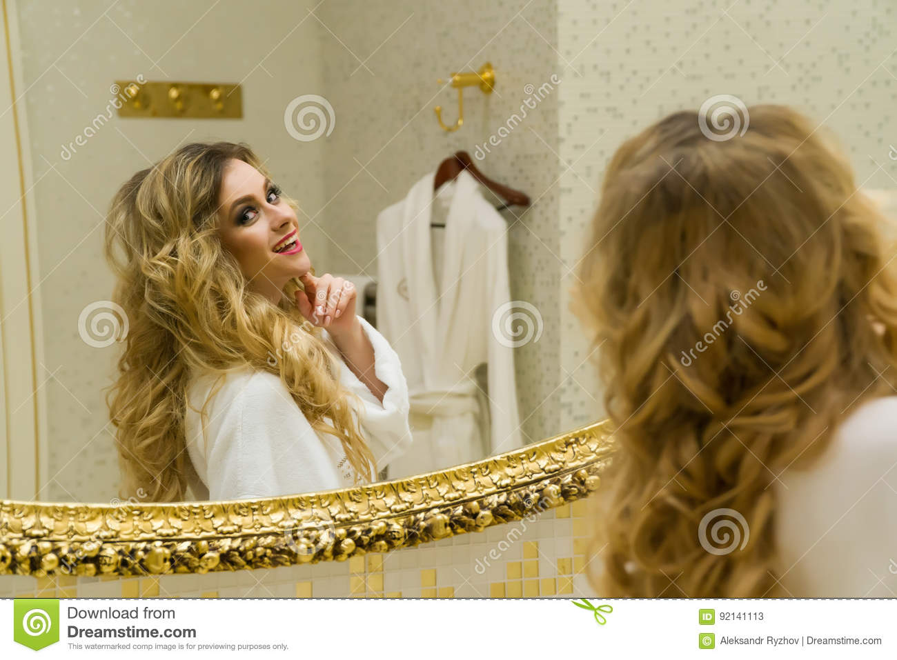 Beautiful blonde girl corrects her hair and looking in the mirror in her bathroom. Beauty young woman corrects her hair