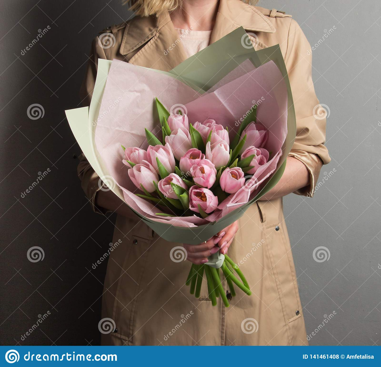 Beautiful blonde girl with curls holding a lush bouquet of flowersbeautiful blonde girl holding a lush bouquet