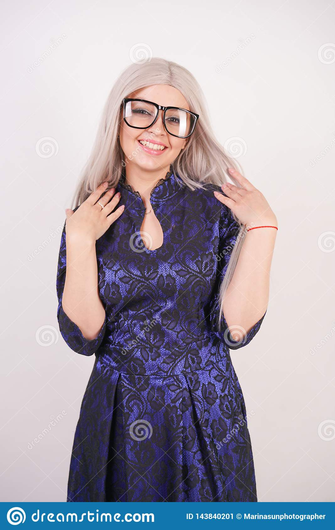 Beautiful blonde girl with glasses in luxurious blue with black lace evening dress on white background in Studio