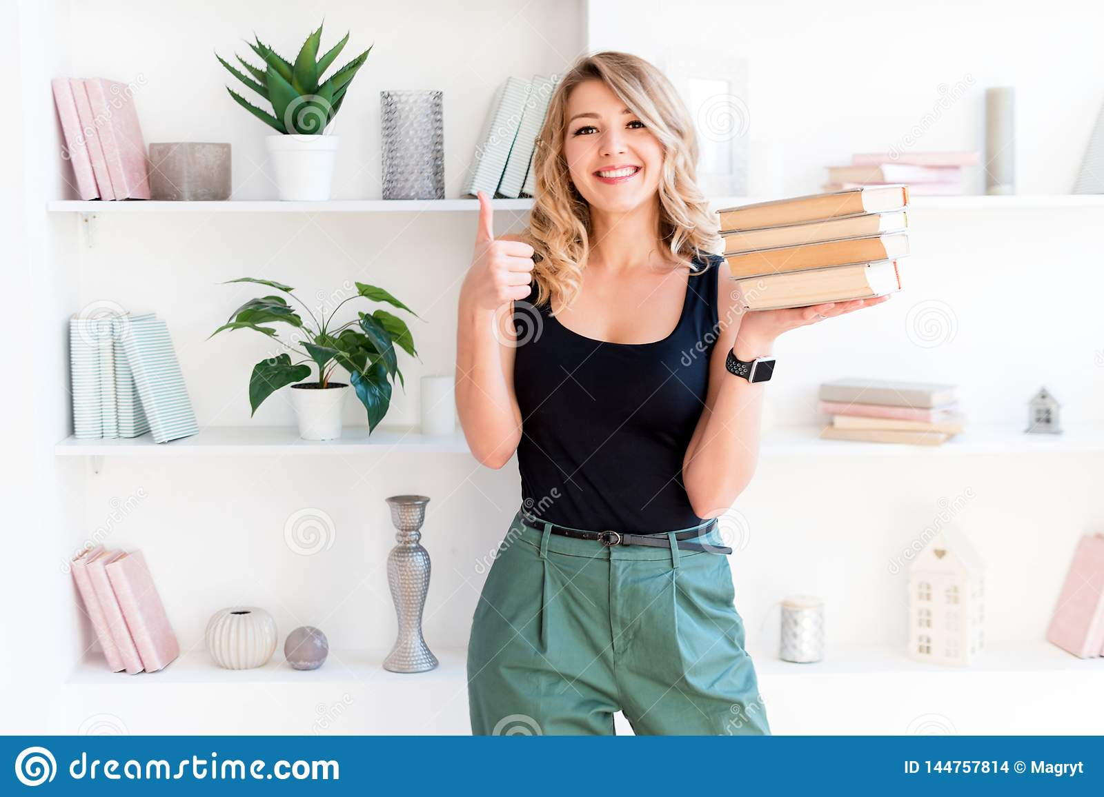 Beautiful blonde girl holding a stack of books and showing thumbs up. The concept of education, courses, examinations