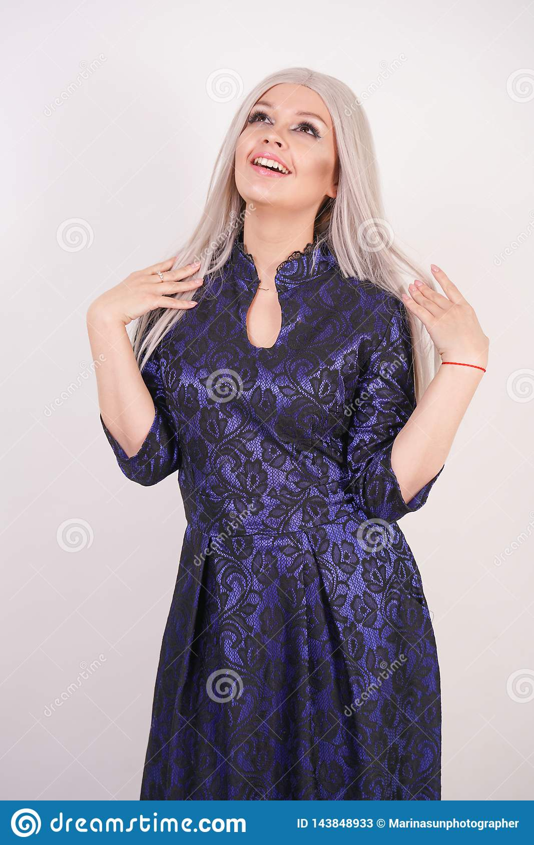Beautiful blonde girl in luxurious blue with black lace evening dress on white background in Studio