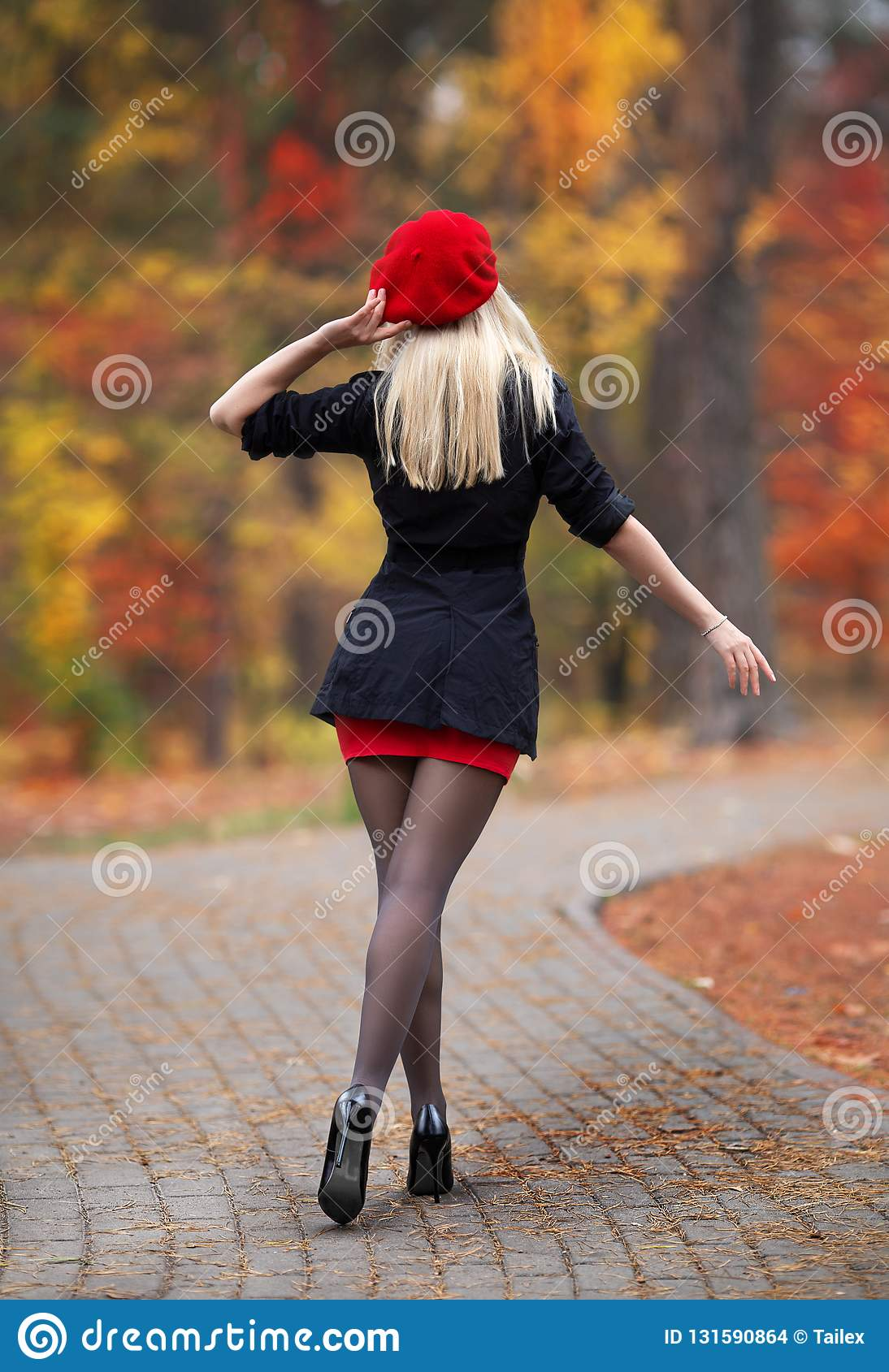 Beautiful blonde girl with perfect legs and red beret posing outdoor on the  street of autumn park. Modern Little Red Riding Hood in the forest 7e8c6237400