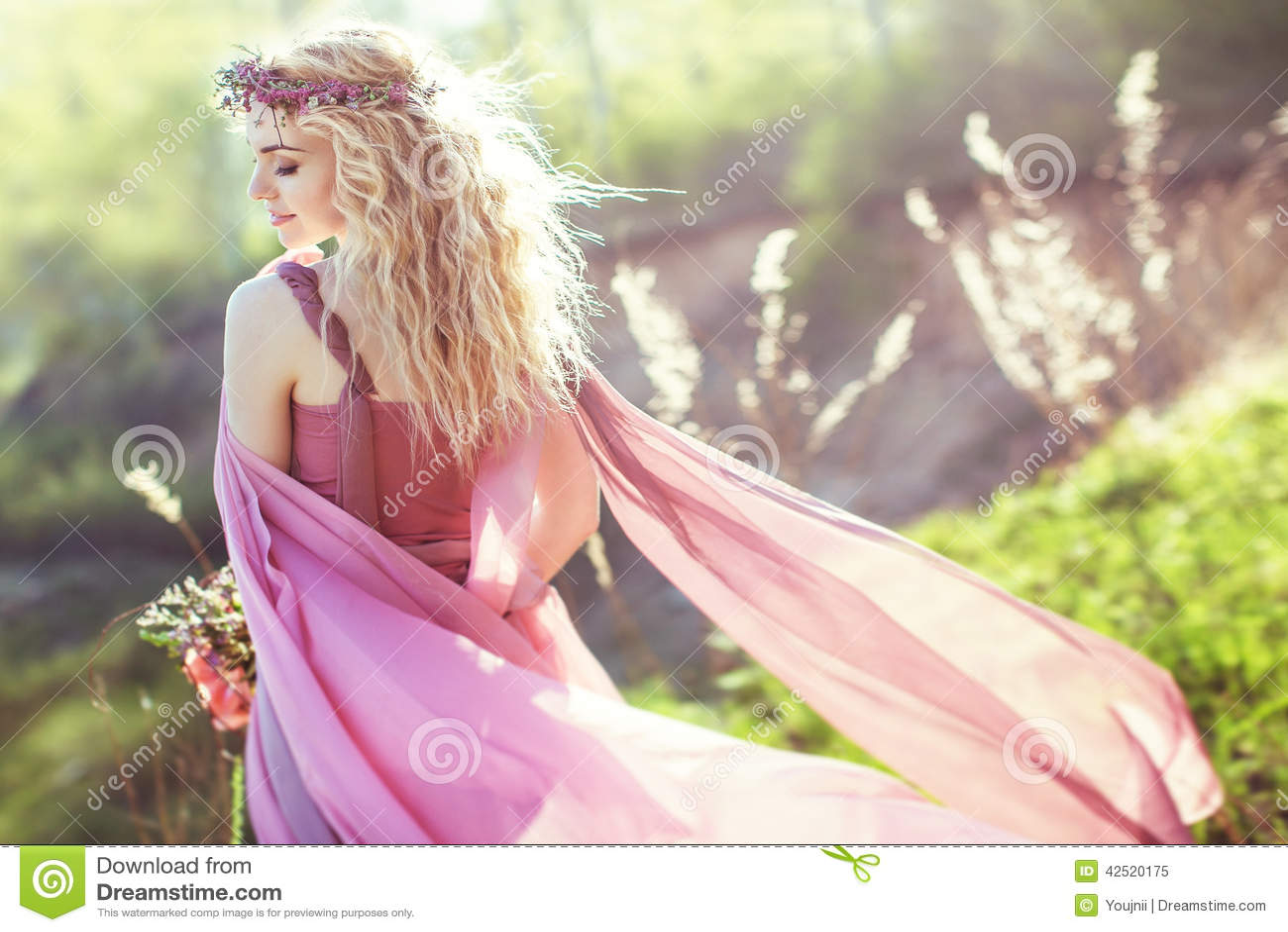 Beautiful blonde girl in pink long dress