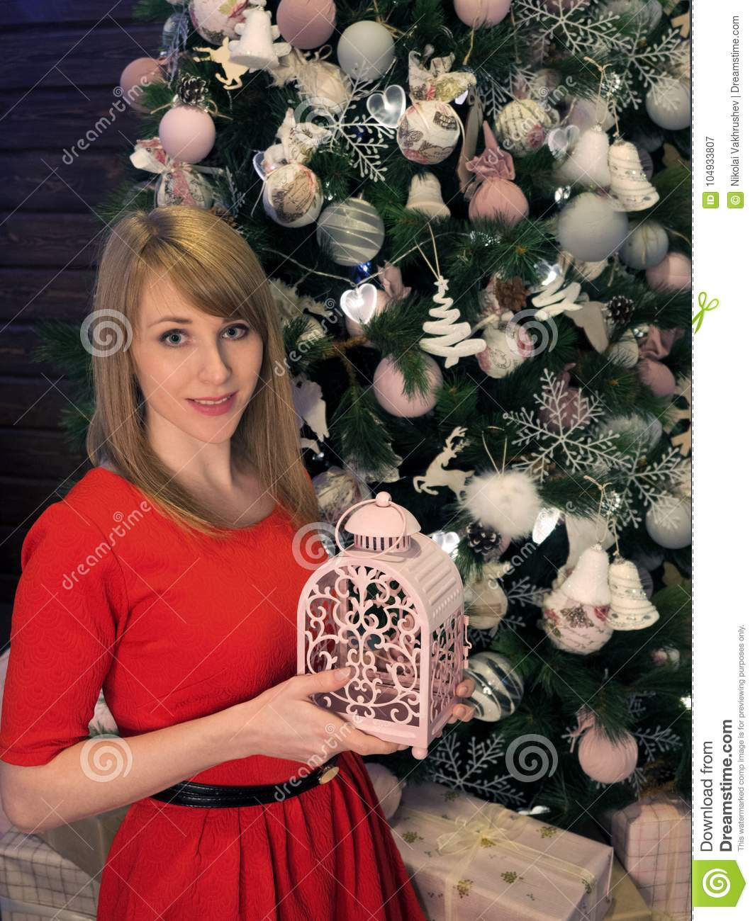 Beautiful blonde girl in red dress and New Year presents. New Year mood and interior.