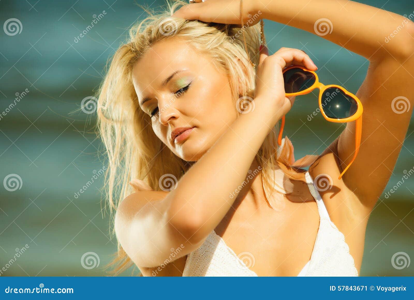 Of blond teen holding sunglasses