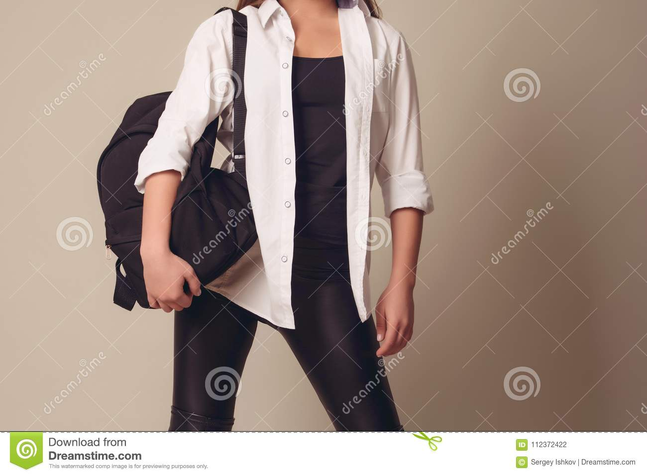 Beautiful blonde girl wearing a white shirt with a leather backpack on her back