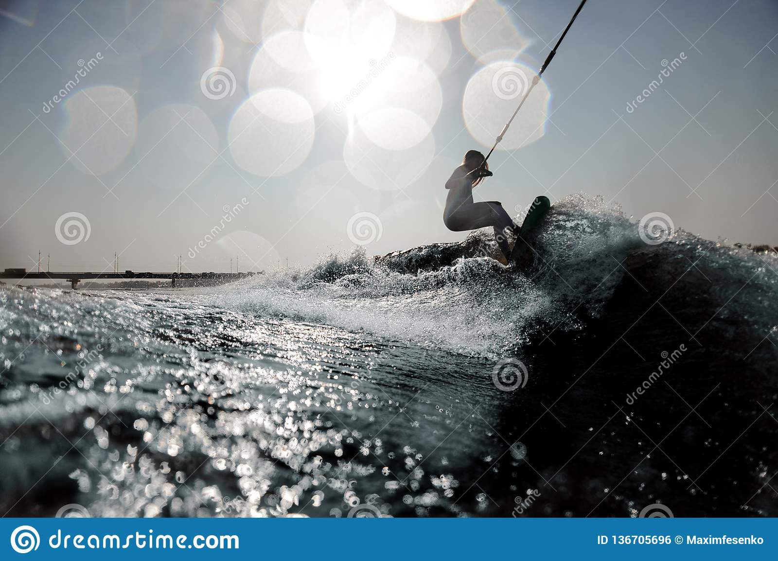 Blonde girl riding on the wakeboard holding a rope