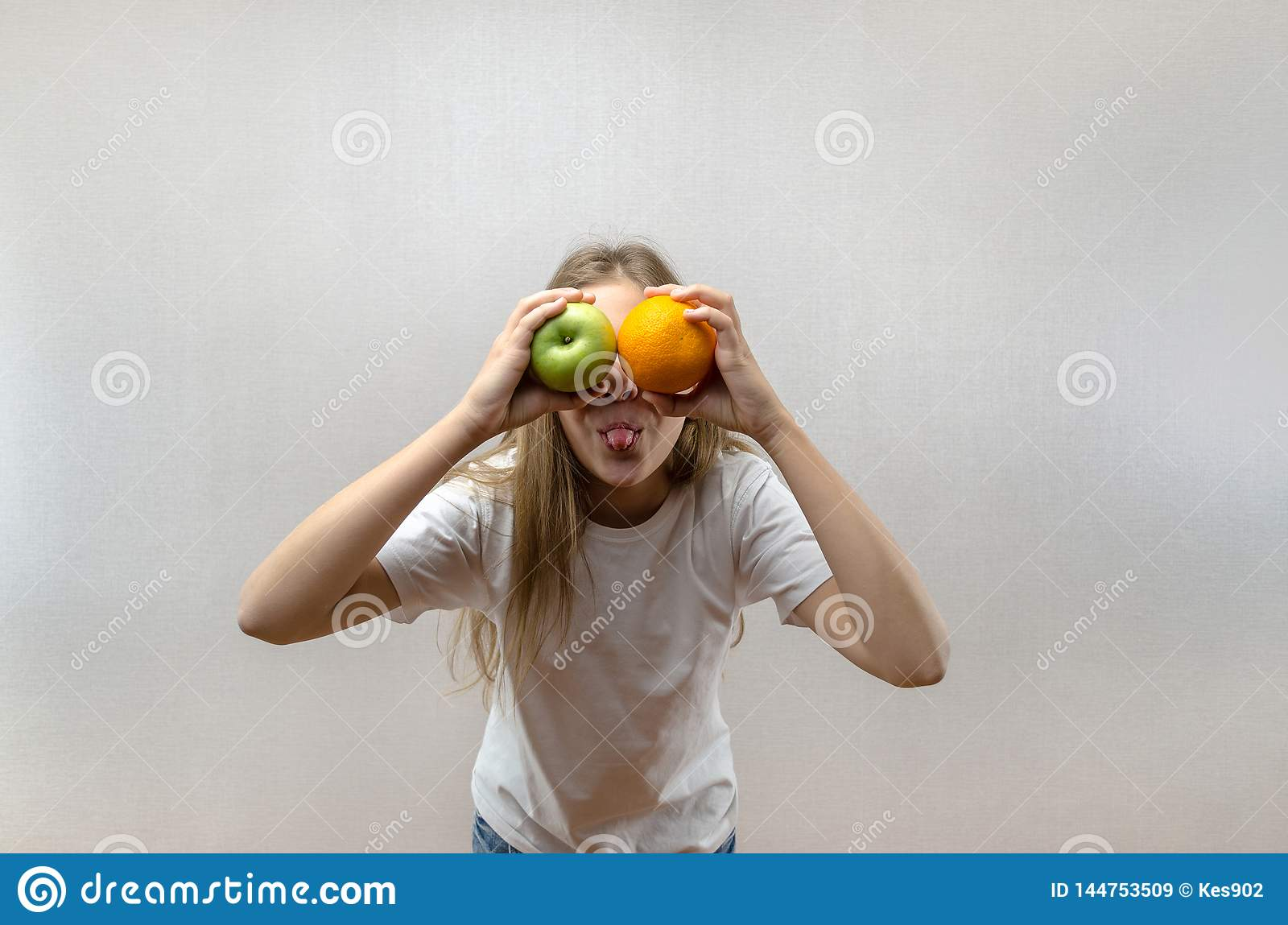 A beautiful blonde girl in a white T-shirt shows her tongue and is holding an apple and an orange. Health food for schoolchildren