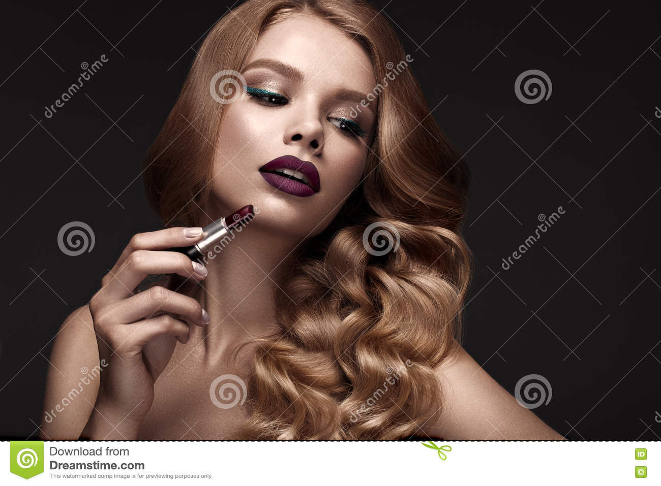 Beautiful blonde in a Hollywood manner with curls, dark lips, lipstick in hand. Beauty face and hair.