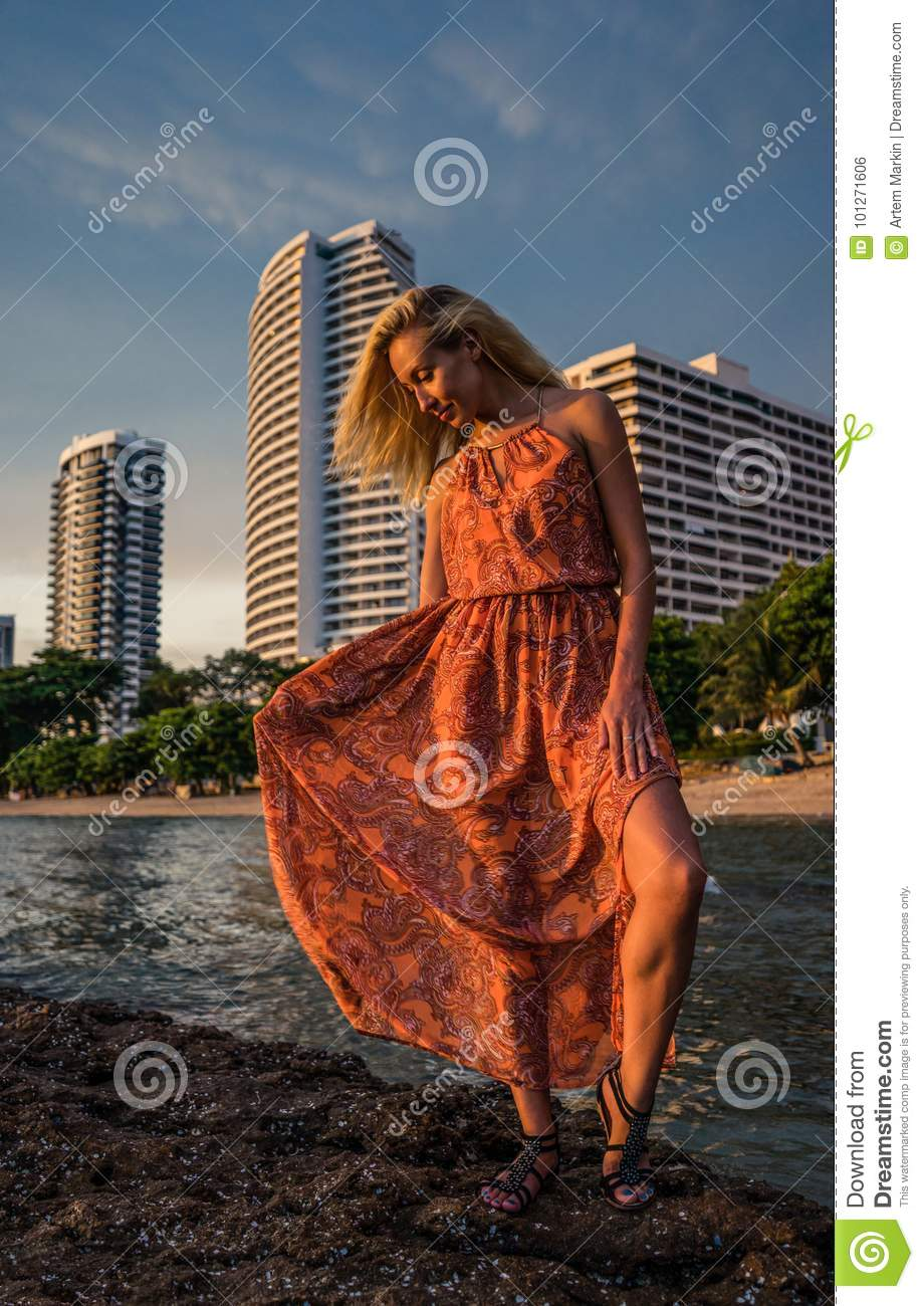 Beautiful blonde in a light red dress stands by the sea on the backdrop luxurious resort in the late afternoon sunlight