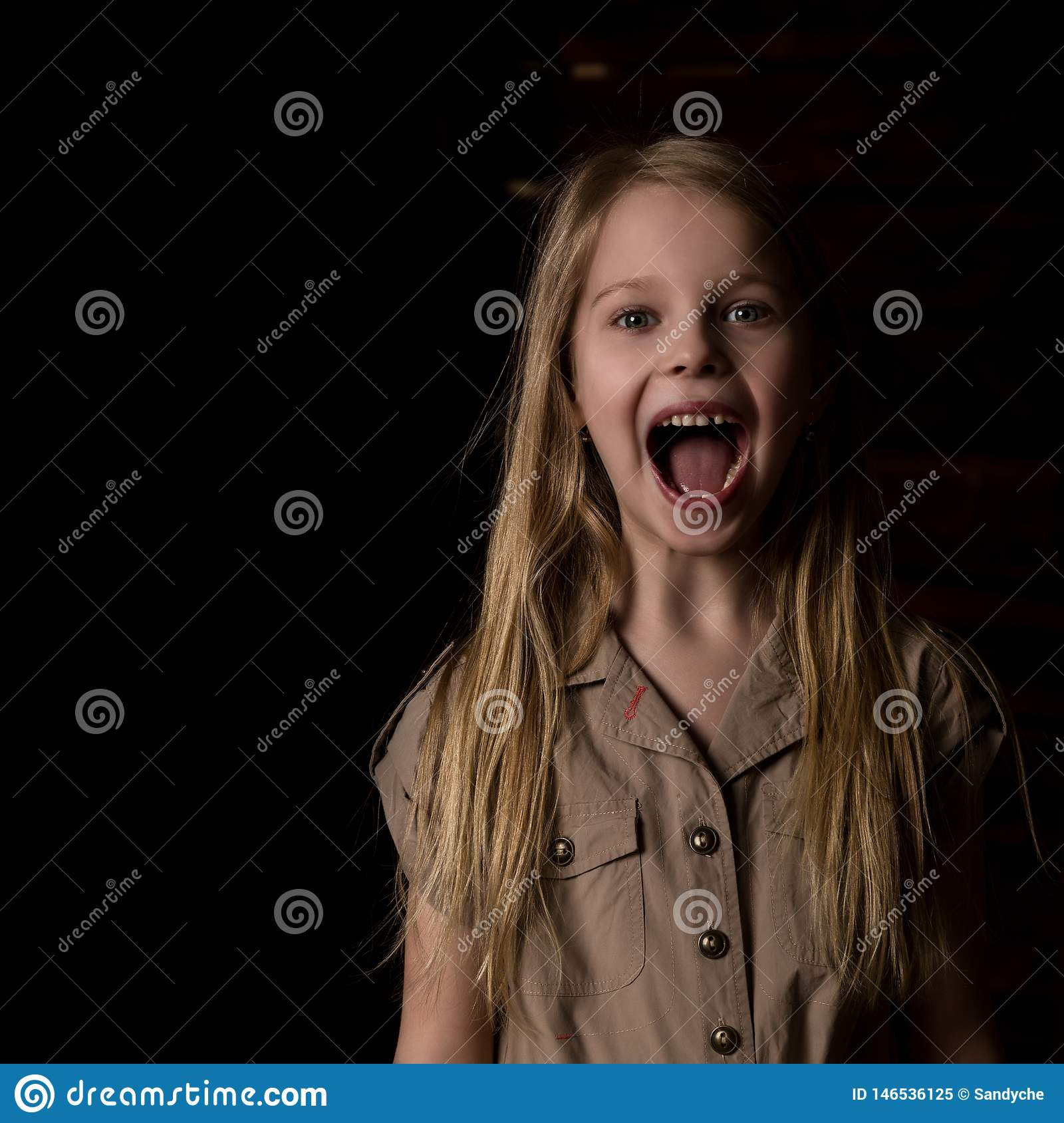 Beautiful blonde little girl on a dark background. She stands in different poses and shows different emotions. free