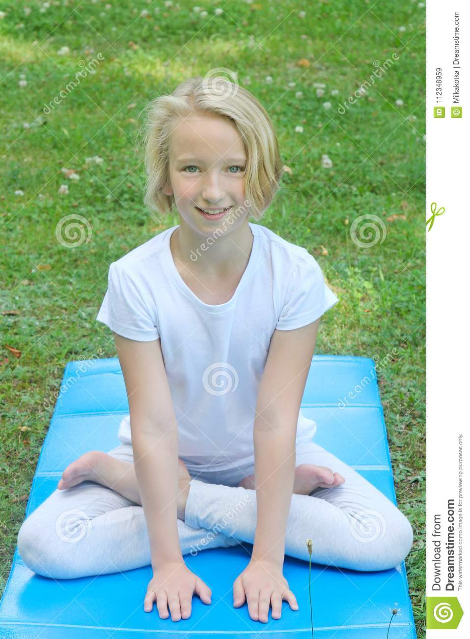 Beautiful Blonde Preteen Girl Practicing Yoga On A Mat In