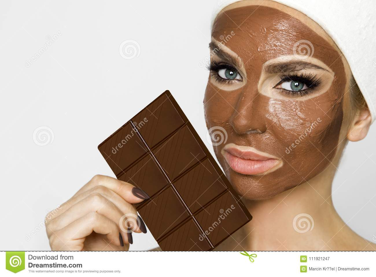 Beautiful blonde woman with a facial mask, beauty spa.Chocolate face mask