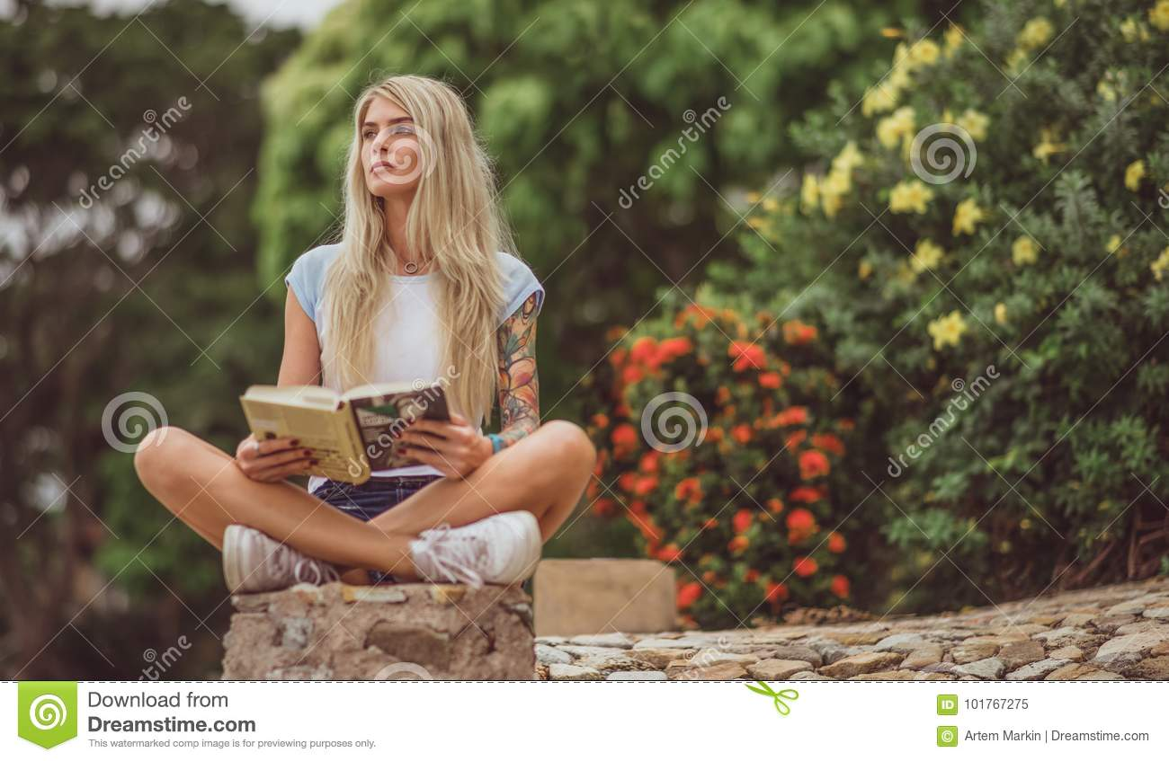 Beautiful blonde sitting in the flower garden and reading a book. Arms tattooed. modern, trendy student