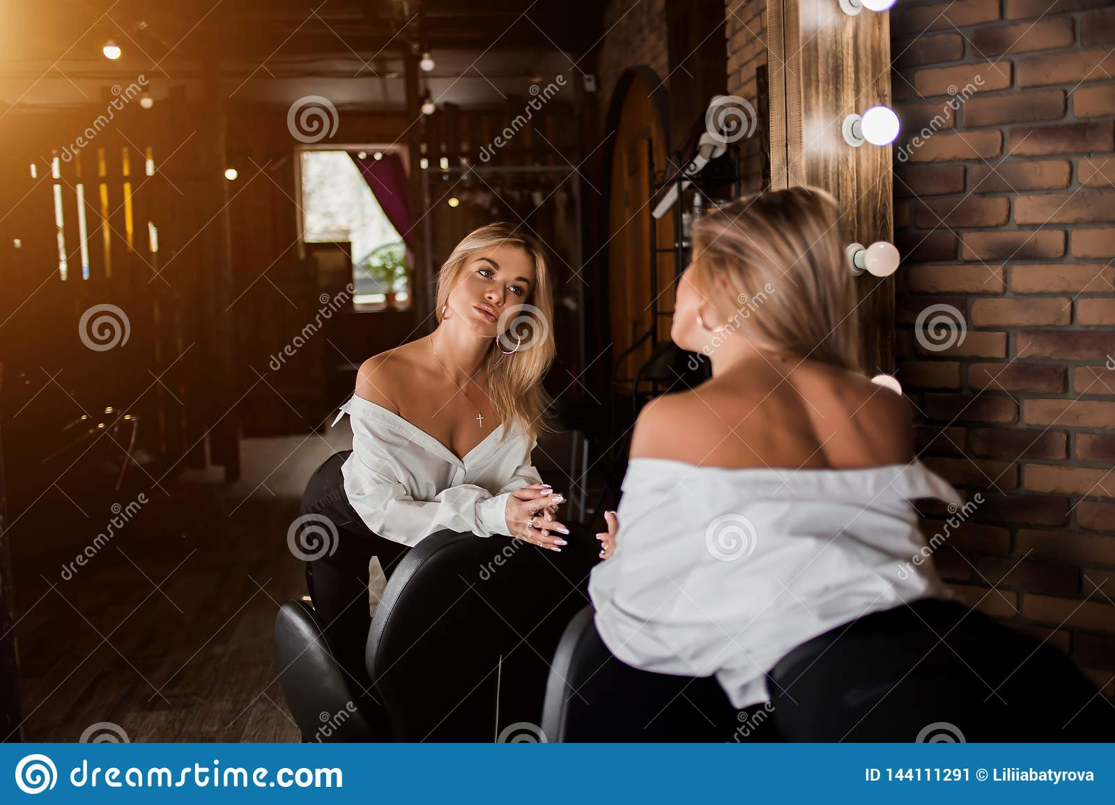 Beautiful blonde woman looking at her reflection in the mirror in beauty salon and checking new haircut and makeup. Beauty salon,