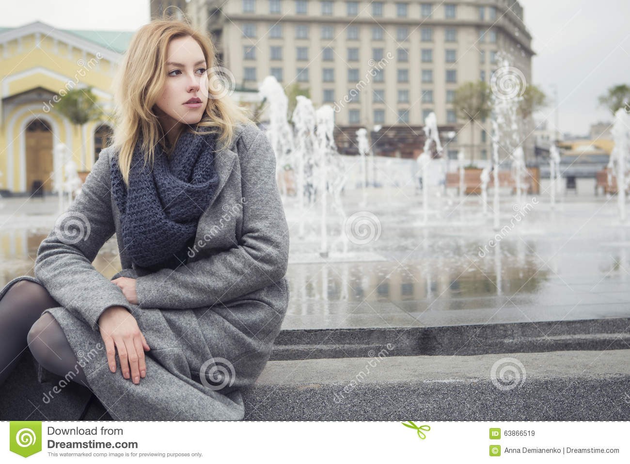 Beautiful blonde young caucasian woman in grey coat and scarf wa