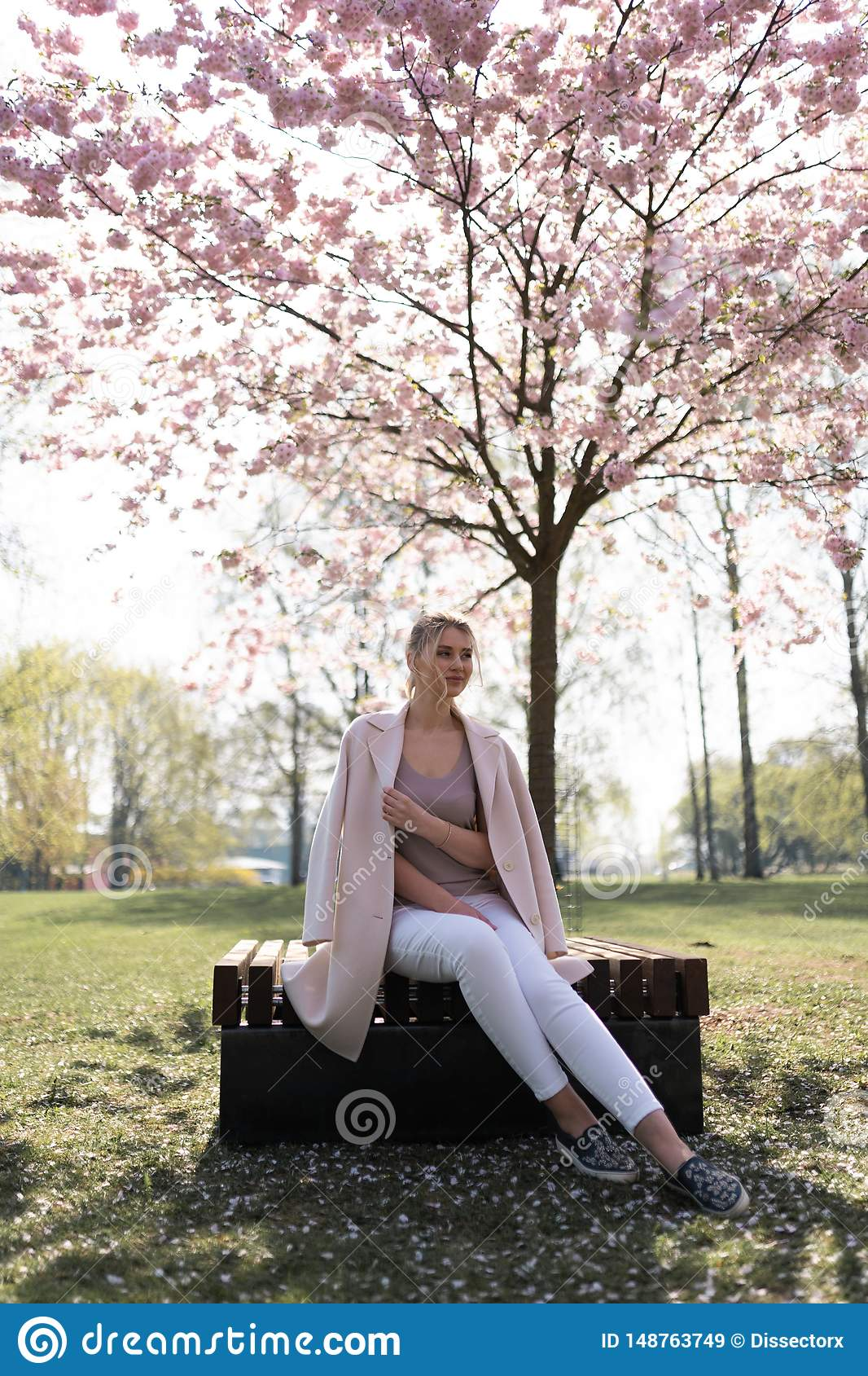 Beautiful blonde young woman in Sakura Cherry Blossom park in Spring enjoying nature and free time during her traveling