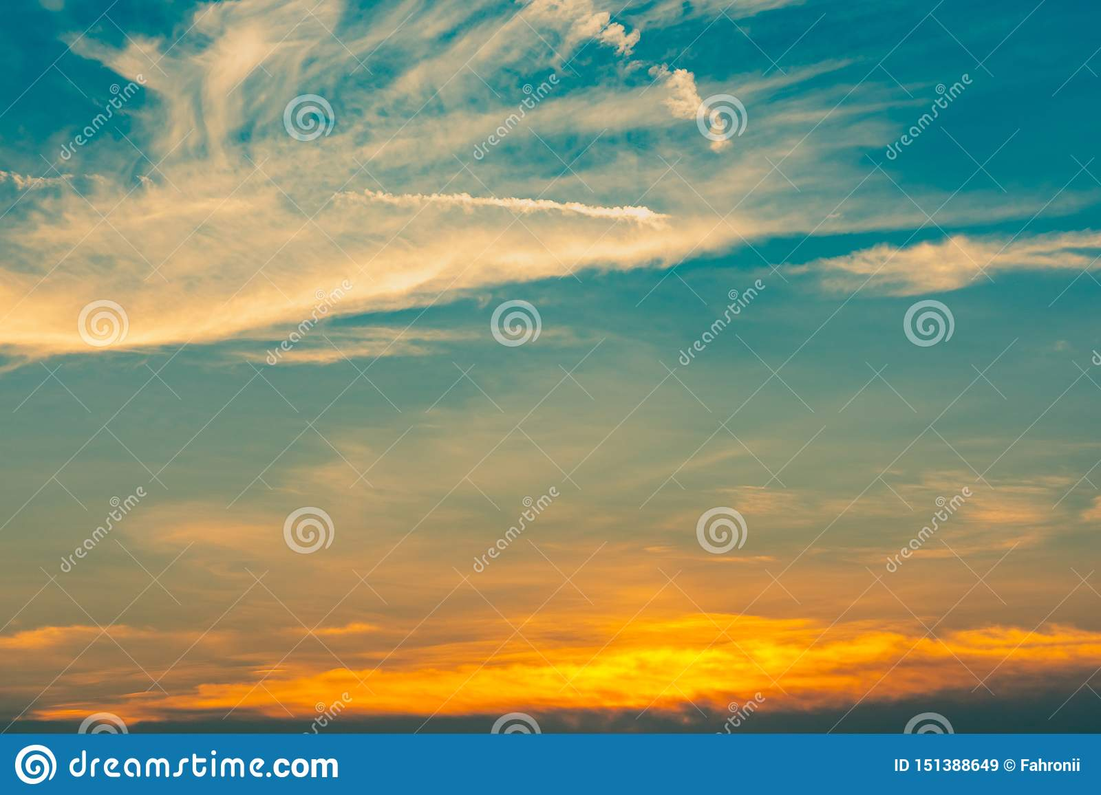 Beautiful blue and golden sky and clouds abstract background. Yellow-orange clouds on sunset sky. Warm weather background. Art