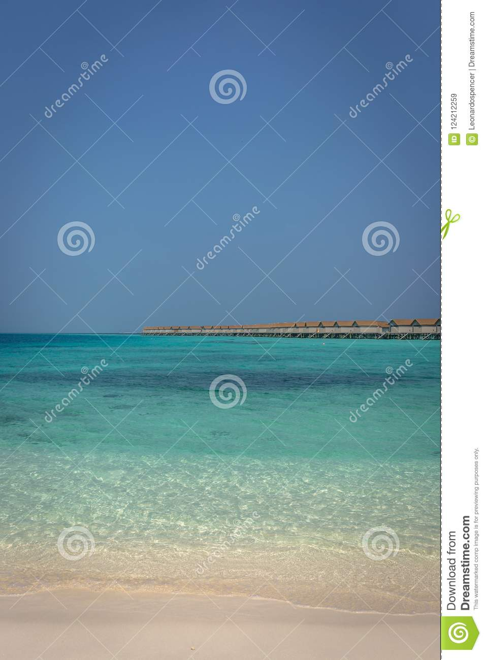Beautiful blue water beach in a tropical paradise, with bungalows in the background in Maldives