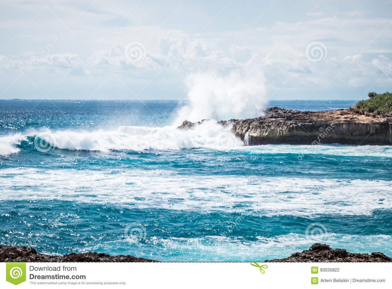 A beautiful blue wave crashes down at the rocks in Devil`s Tear, tropical island Nusa Lembongan, Indonesia, Asia. Sunny