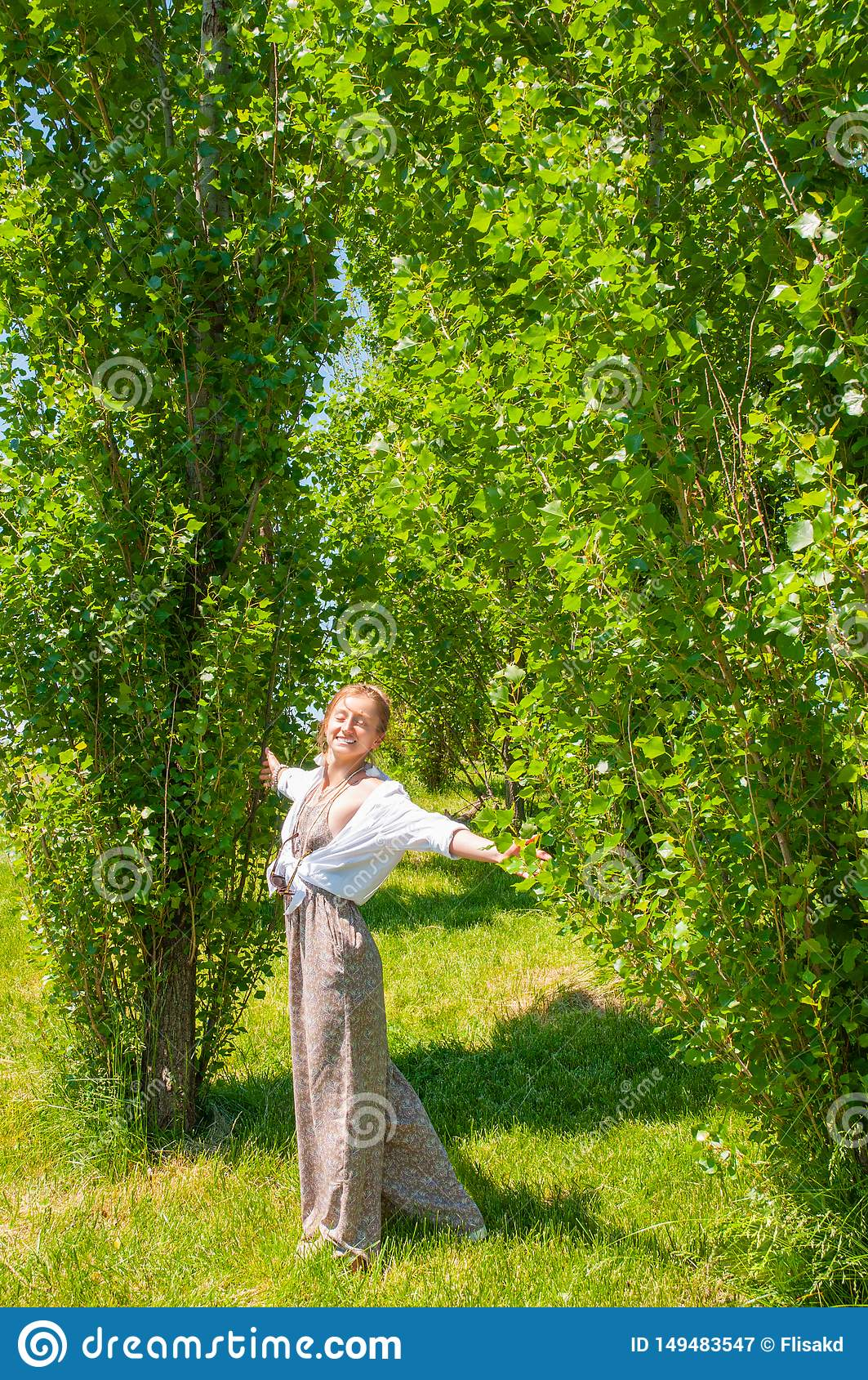 Beautiful boho style woman in fashionable jumpsuit enjoying summer time in park