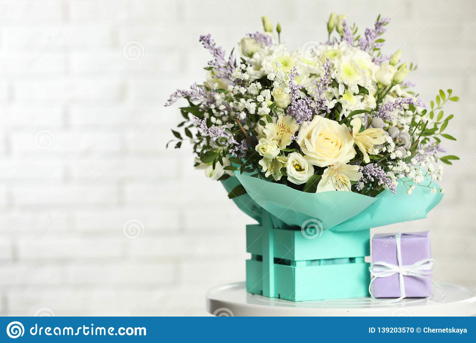 Beautiful bouquet of flowers and gift box on table against light background.