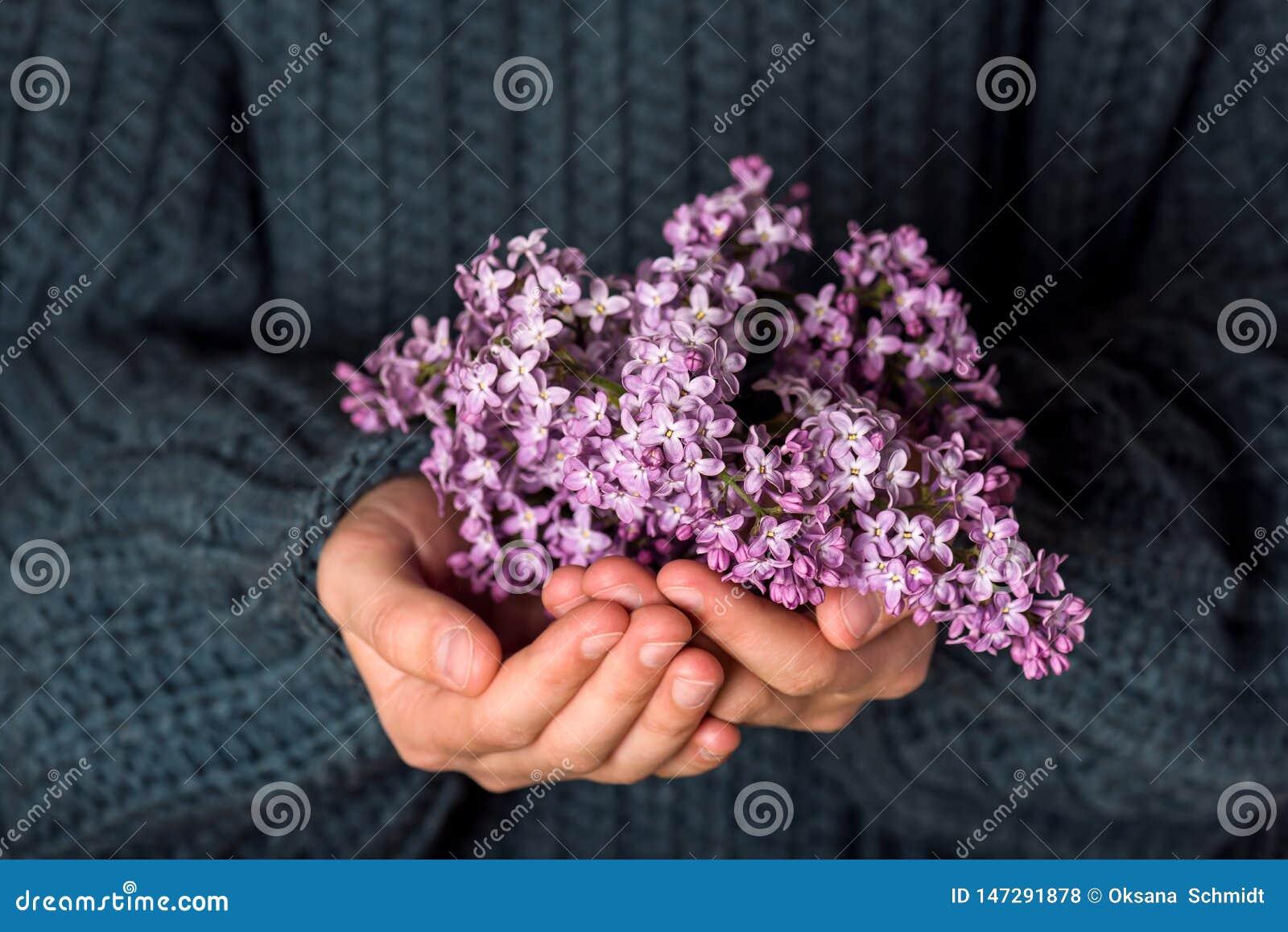 Beautiful bouquet of purple lilac flowers in girls hands.